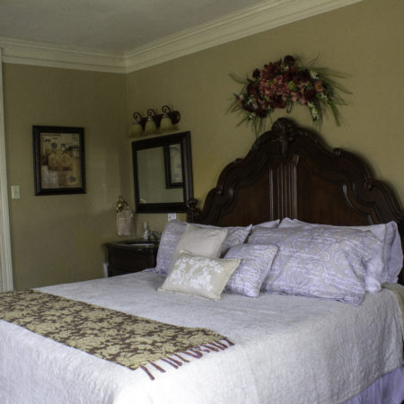 Beige guest room with blue carpeting, scalloped bed topped with red bedding, built-in window seat and desk