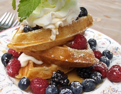 close-up view of golden waffles drizzled in syrup and topped with fresh red and blackberries and whipped cream
