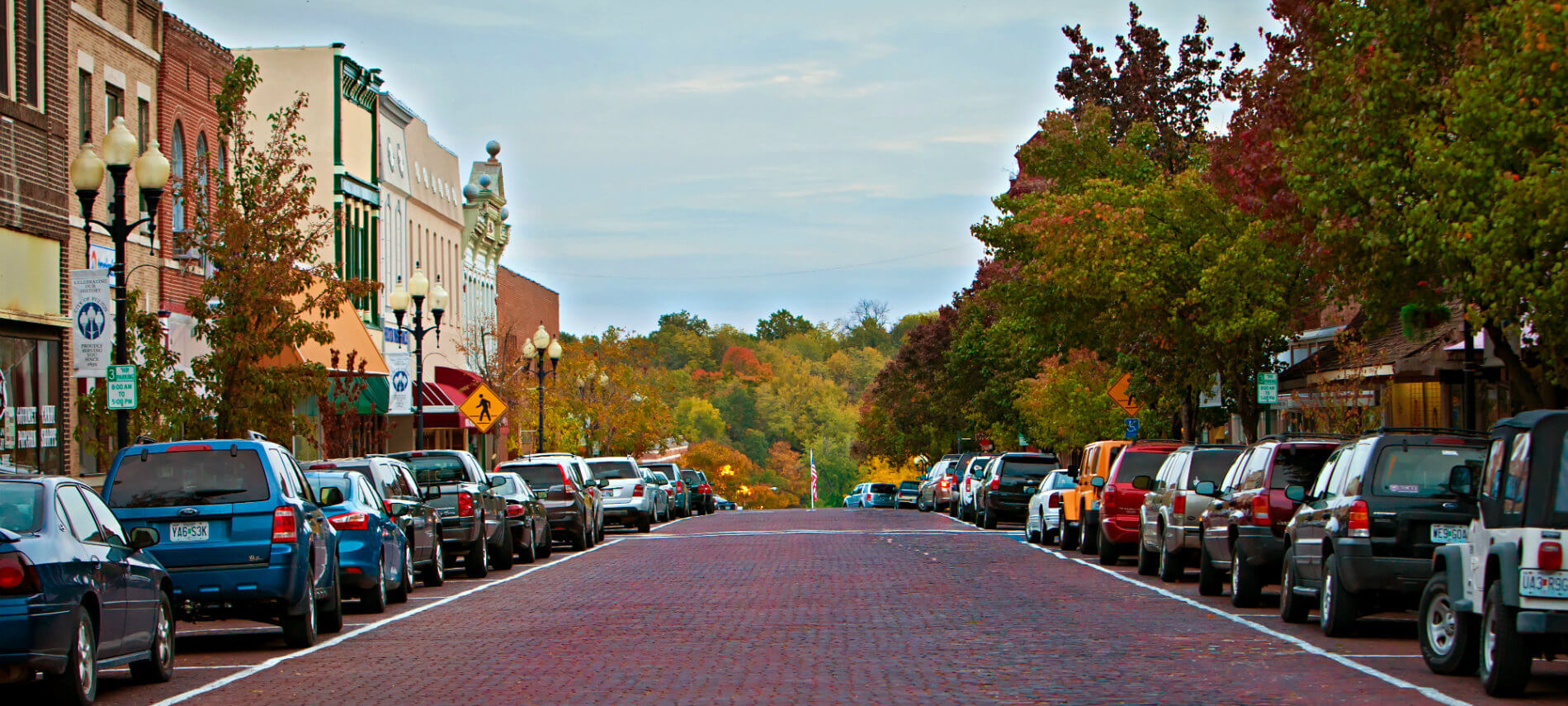 Red brick city street lined with parked cars, old brick storefronts and trees in rich autumn hues