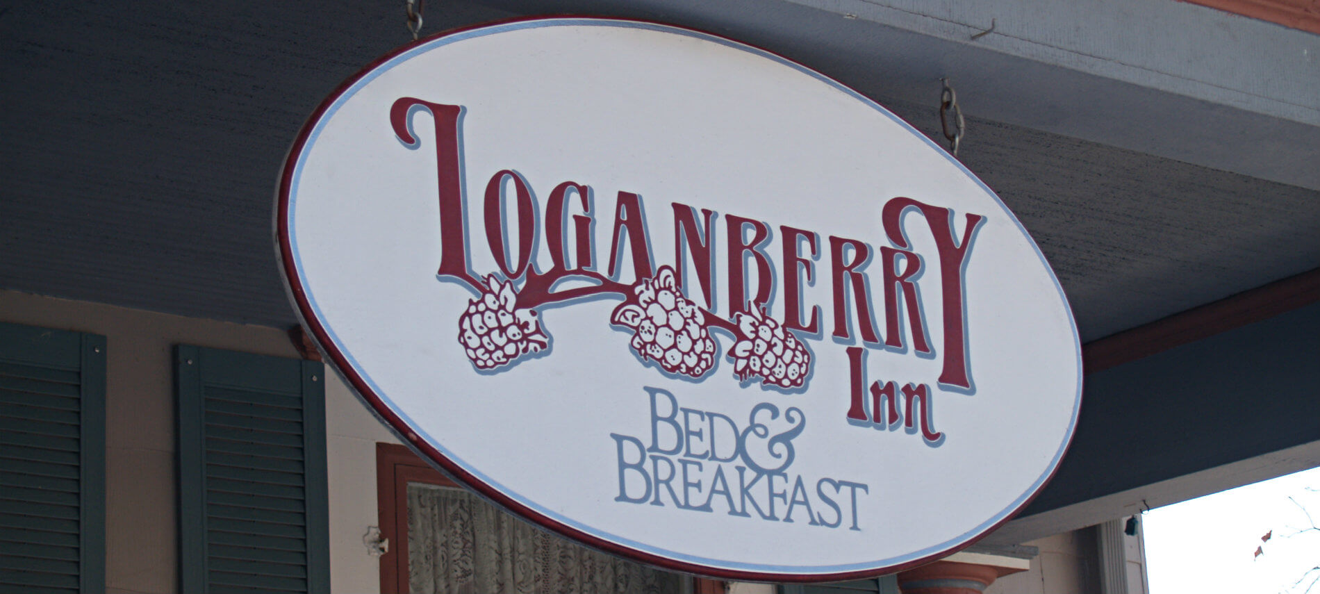 Close-up view of a white oval sign hanging from the front porch that says Loganberry Inn Bed & Breakfast in red and blue