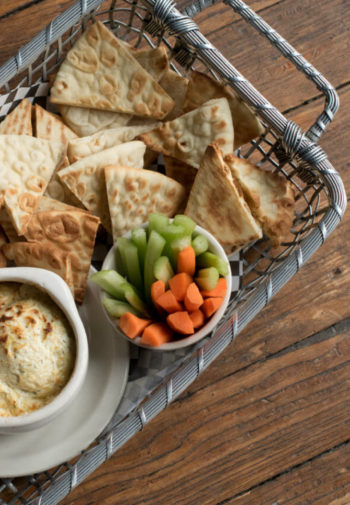 Gray basket filled with homemade pitz wedges, fresh carrot and celery sticks and baked dip
