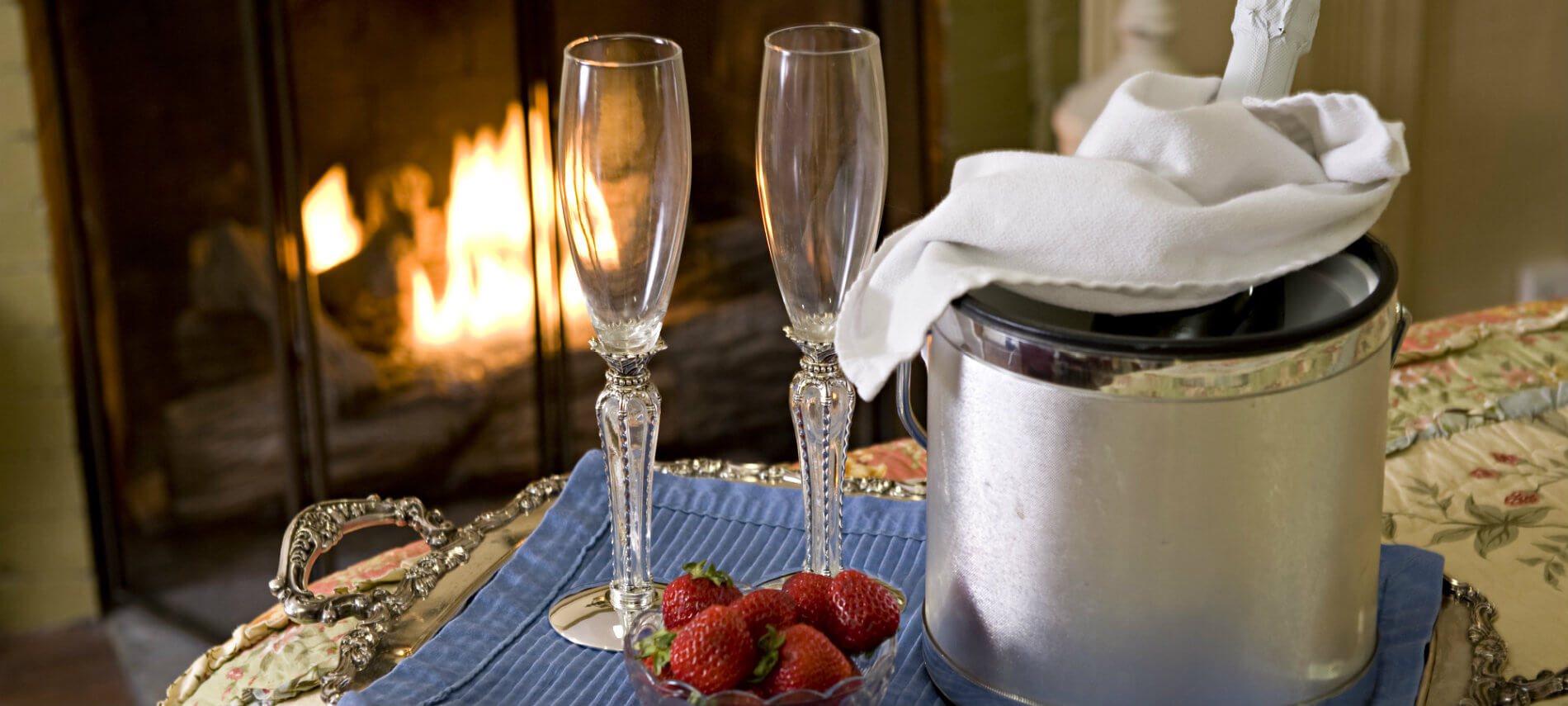 Tray topped with two champagne flutes, ice bucket with champagne, fresh strawberries, in front of a warm fire