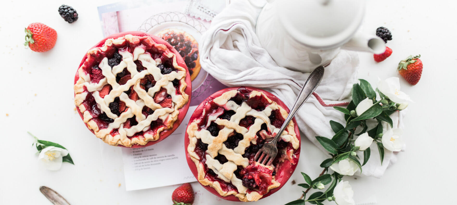 Table with two personal sized berry pies, white carafe, printed recipe, white towel, surrounded by fresh berries and flowers