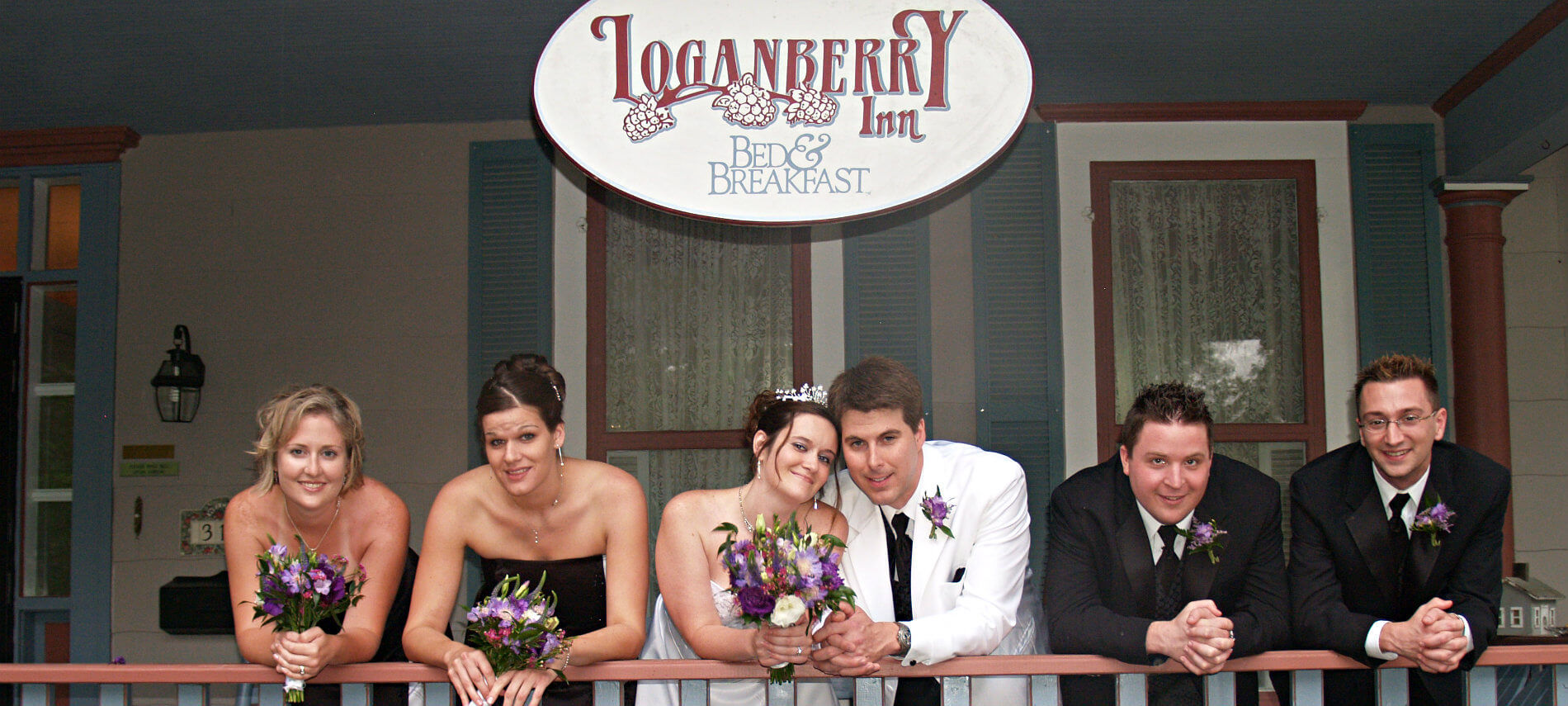 Bride and groom in white, maids of honor and groomsmen in black, smiling on the porch under the Loganberry Inn sign
