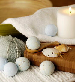 Several bath bombs next to a white lit candle, white towel, a few seashells and a body sponge