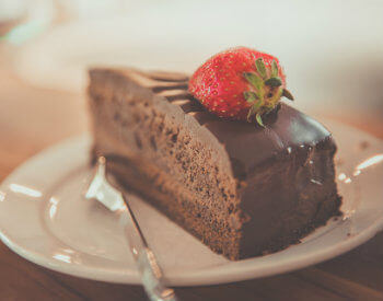 Slice of rich chocoloate cake topped with a fresh red strawberry