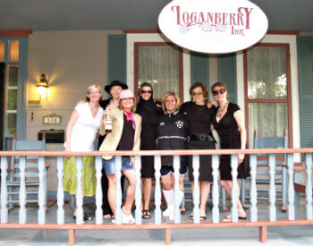 Seven women standing on the Inn's front porch underneath the Loganberry Inn sign