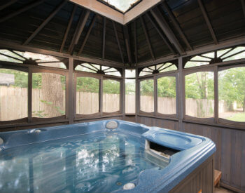 Blue hot tub filled with water situated under a covered wood gazebo-like structure