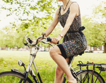 Woman riding a bicycle surrounded by lush greenery