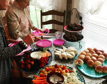 Two women filling their plates from a table topped with fresh veggies, tea sandwiches, fresh fruit and brownies