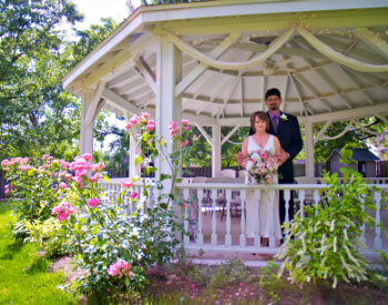 Bride and groom standing under a large white gazebol surrounded by green trees and grass and colorful pink flowers