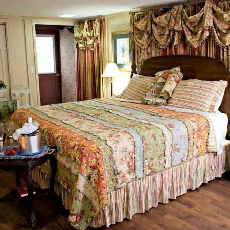 Cozy guest room with hardwood floors, colorful pastel quilt and bedskirt, dinette for two, and table with champagne and strawberries