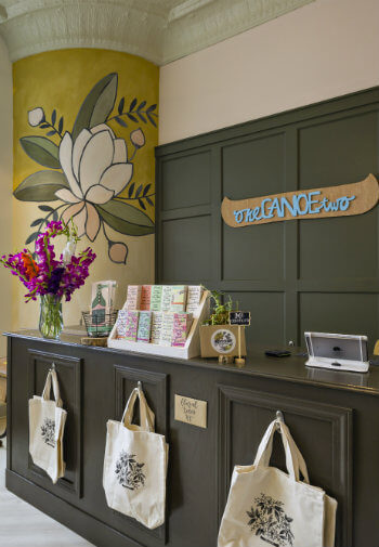 A store customer service desk with canvas bags for sale, pamplets to read, and fresh red and pink flowers in a vase
