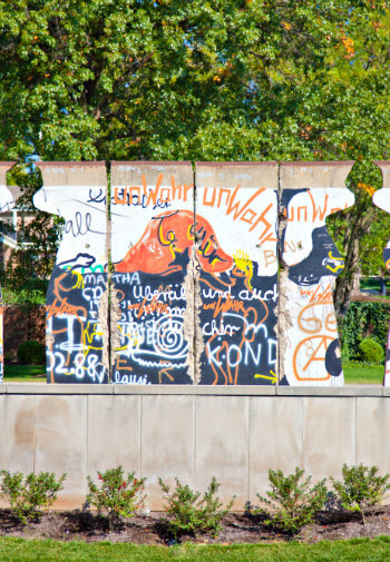 Street side wall with colorful graffiti in blue, orange, and white amidst green trees and shrubs
