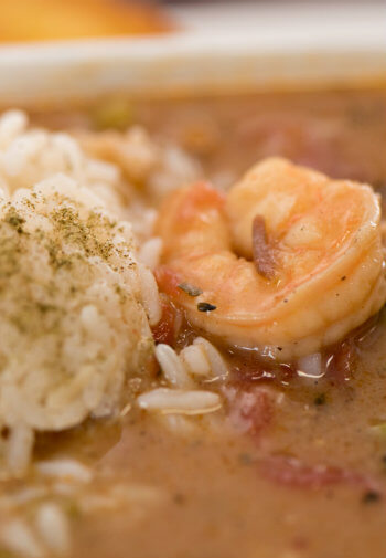 Close-up view of a dish with fresh shrimp, tomatoes, sauce, white rice and seasonings