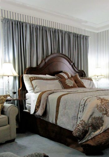 Serene guestroom with scalloped bed placed against a backdrop of gray curtains, nightstands with lamps and cozy chair