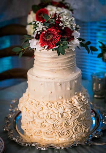 Beautiful, white, three-tiered wedding cake topped with fresh red and white flowers and greenery