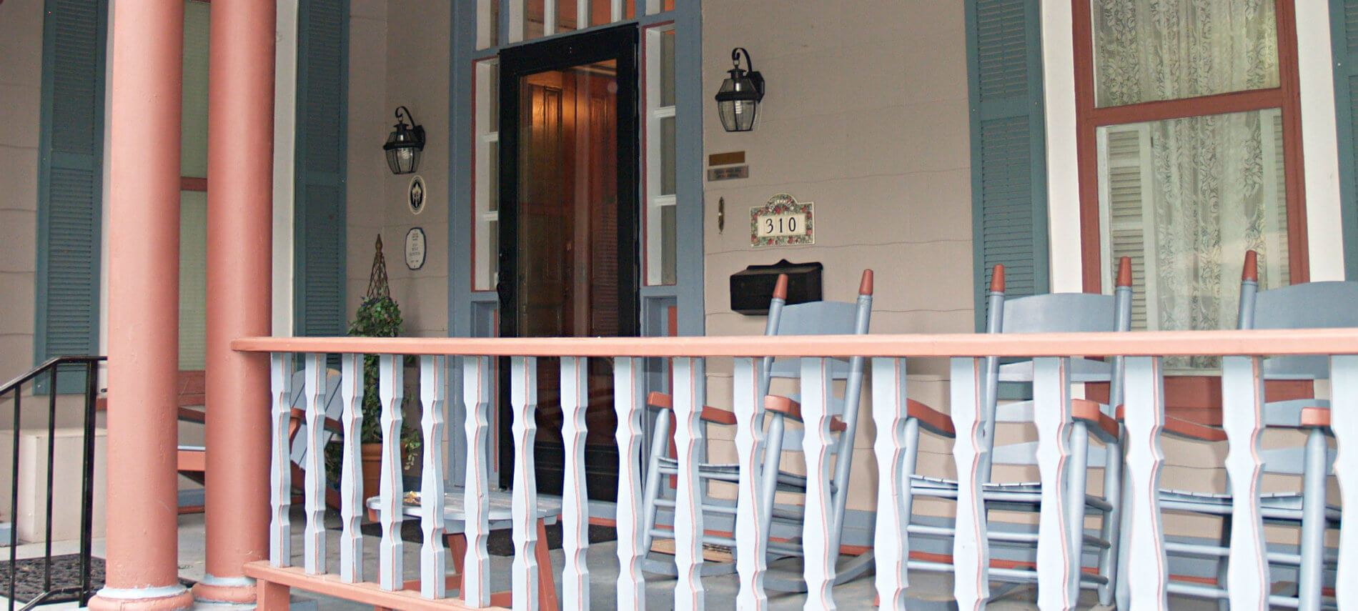 The Inn's covered front porch with several rocking chairs painted teal and rust red