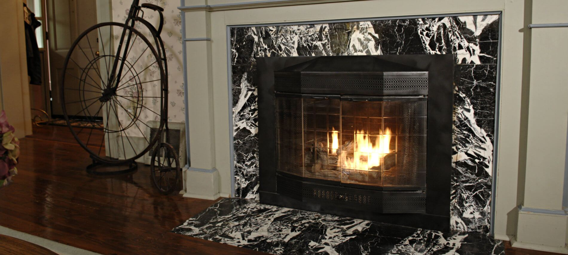 Cozy warm fire in a fireplace with black and white marble and tan painted mantel surround