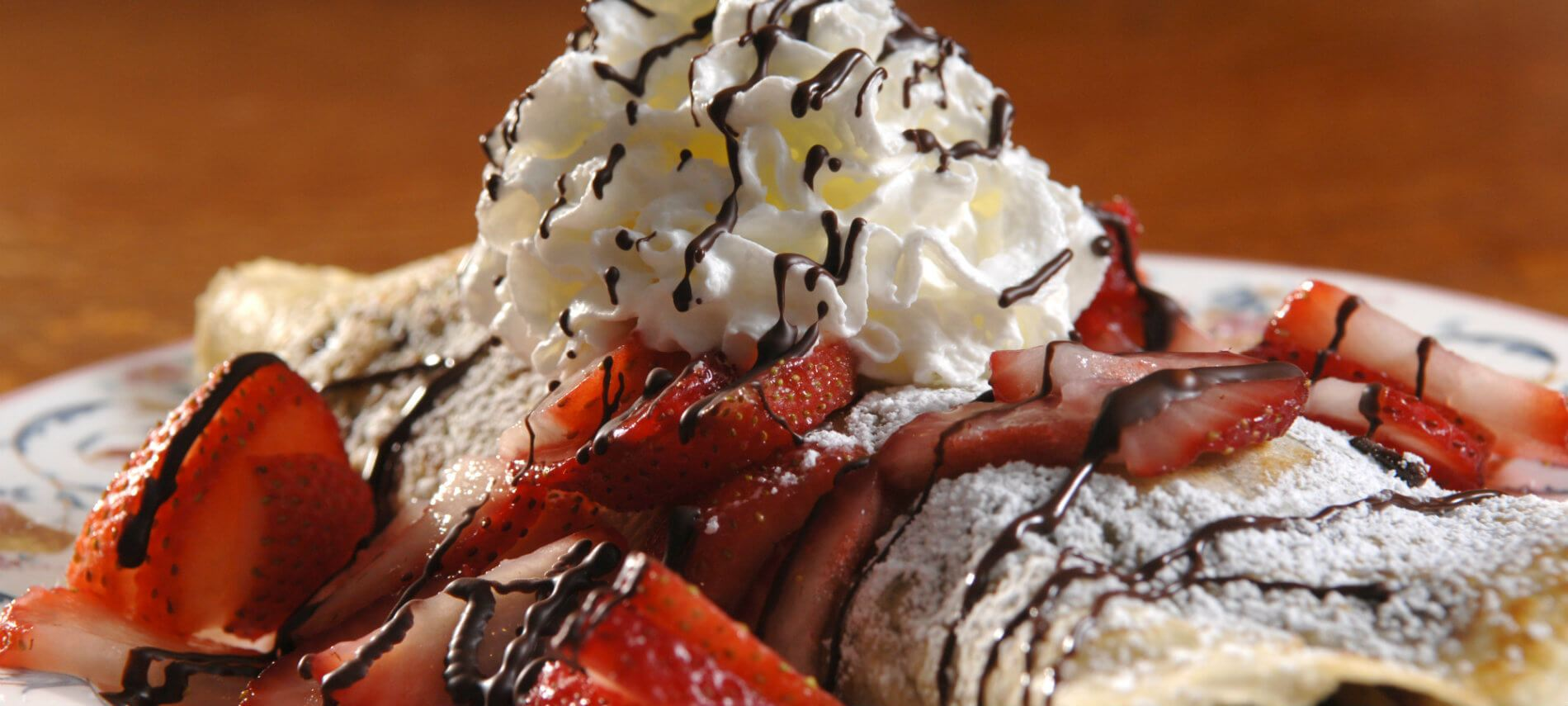 Delicious crepe topped with powdered sugar, whipped cream, fresh strawberries and drizzled in chocolate syrup
