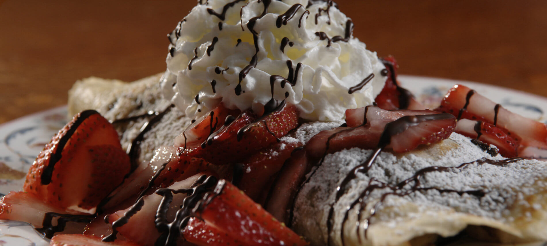Delicious crepe topped with powdered sugar, whipped cream, strawberries and chocolate syrup