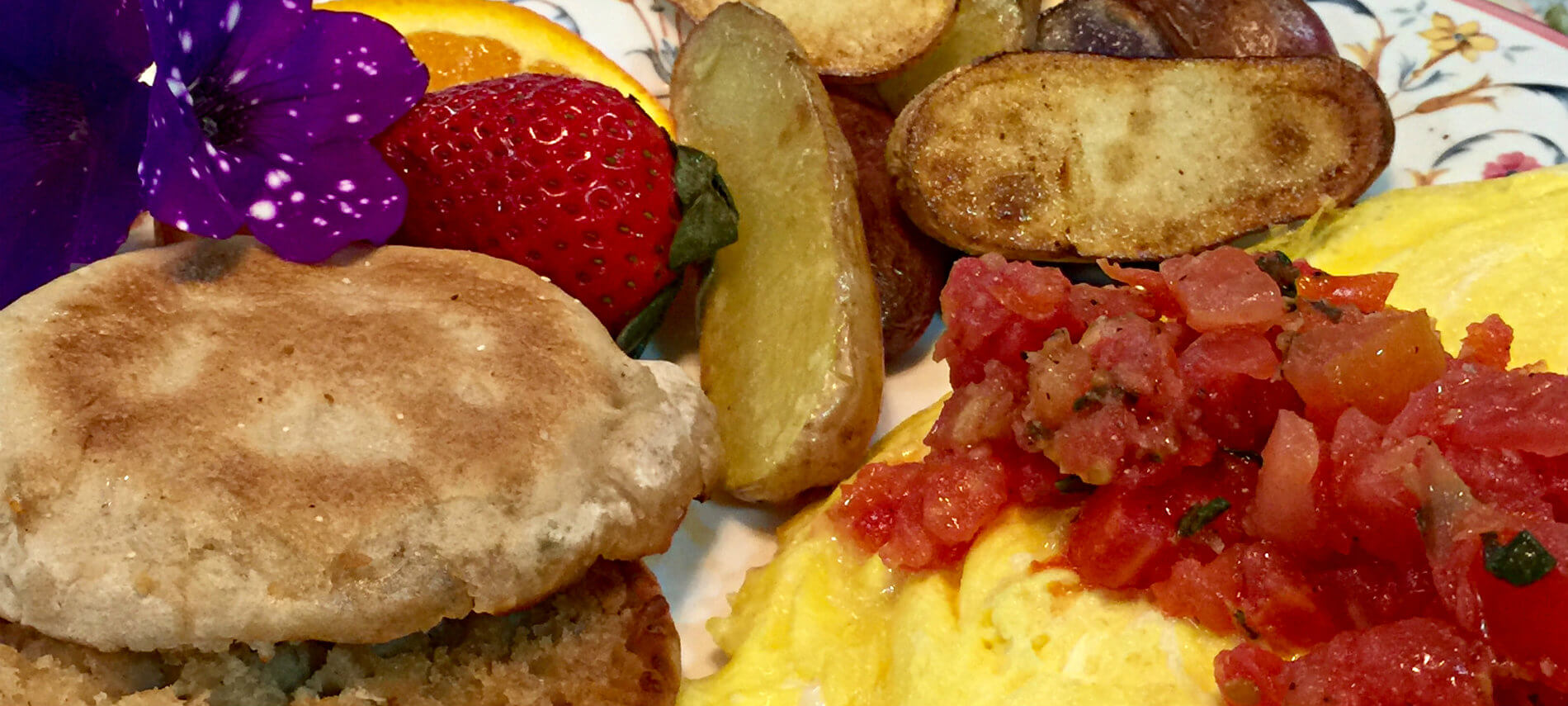 Omelette topped with tomatoes, golden potatoes, fresh fruit and toasted English muffin
